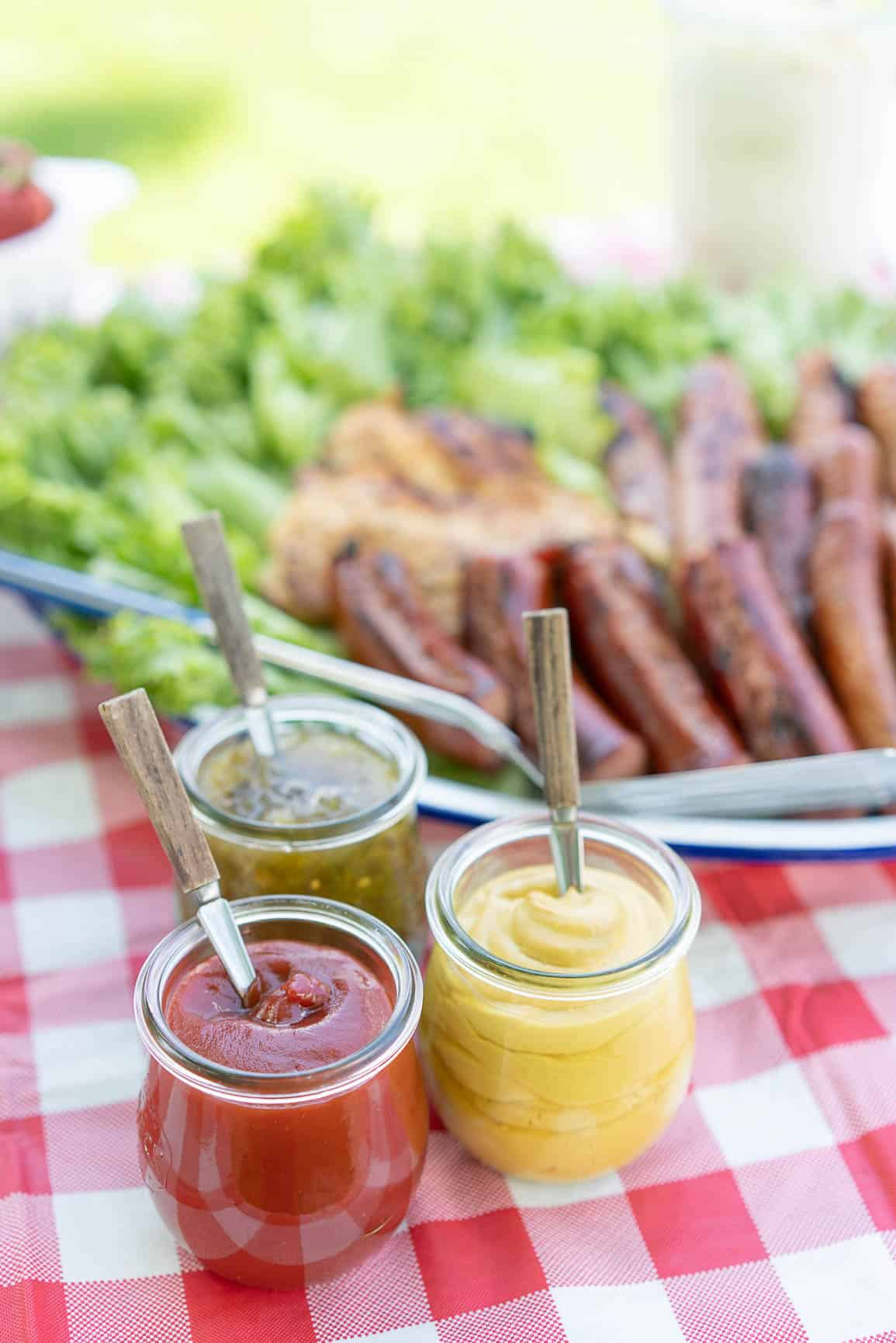 ketchup, mustard and relish in weck jars with spoons on a picnic table