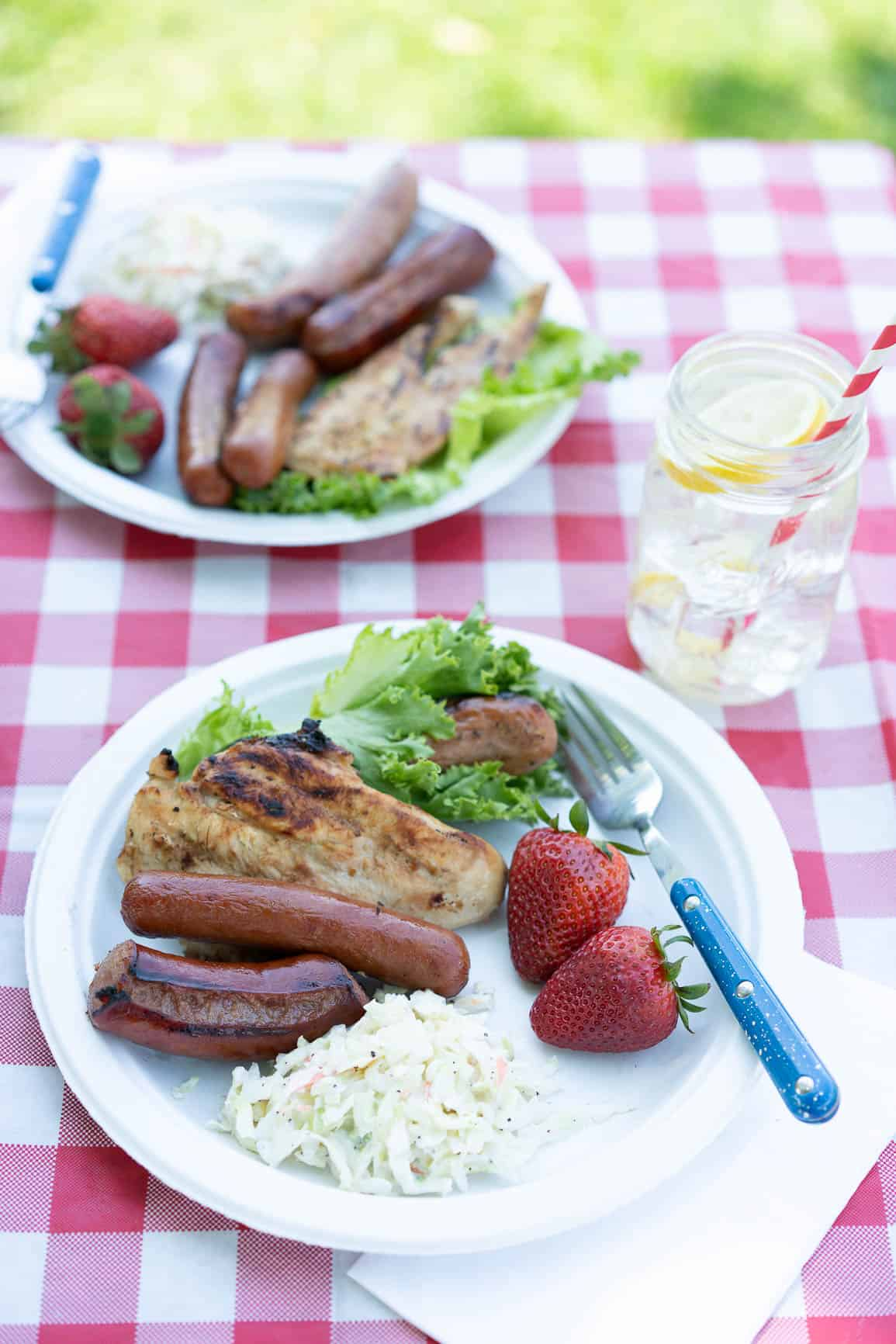 cookout plate of food; hot dogs, kielbasa, chicken, strawberries, and Cole slaw.