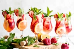 The Best Cocktail of Summer; Sparkling Strawberry Rosé Wine Sangria garnished with mint and lemon.
