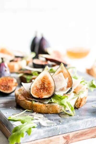 This flavorful Fig Bruschetta is an easy, yet delicious appetizer. It's also perfect for dinner parties, picnics, and any occasion where you want to serve something that is simple yet sophisticated. Toasted bread rubbed with garlic, topped with fresh figs, prosciutto, arugula and features Copper Kettle Cheese, drizzled with honey